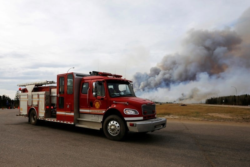 A fire truck drives by the wildfires near Fort McMurray, Alberta, Canada, May 7, 2016. REUTERS/Mark Blinch