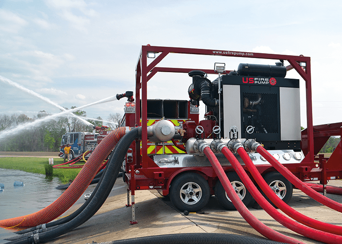 A US Fire Pump 5,500 GPM Mobile Trailer Unit supporting an industrial pumper.