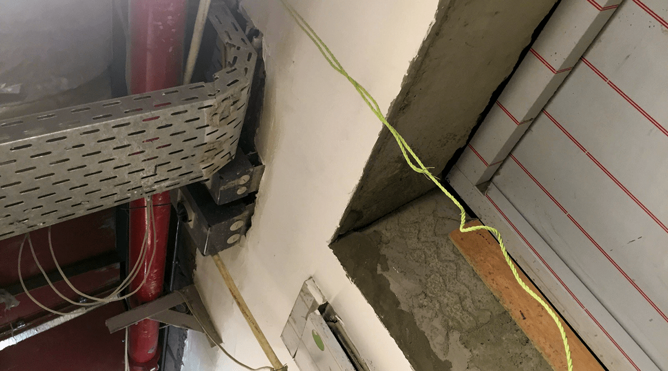 Unsealed horizontal penetration in the service areas of an under construction hotel building. These unsealed penetrations will cause smoke to propagate from one area to another.
