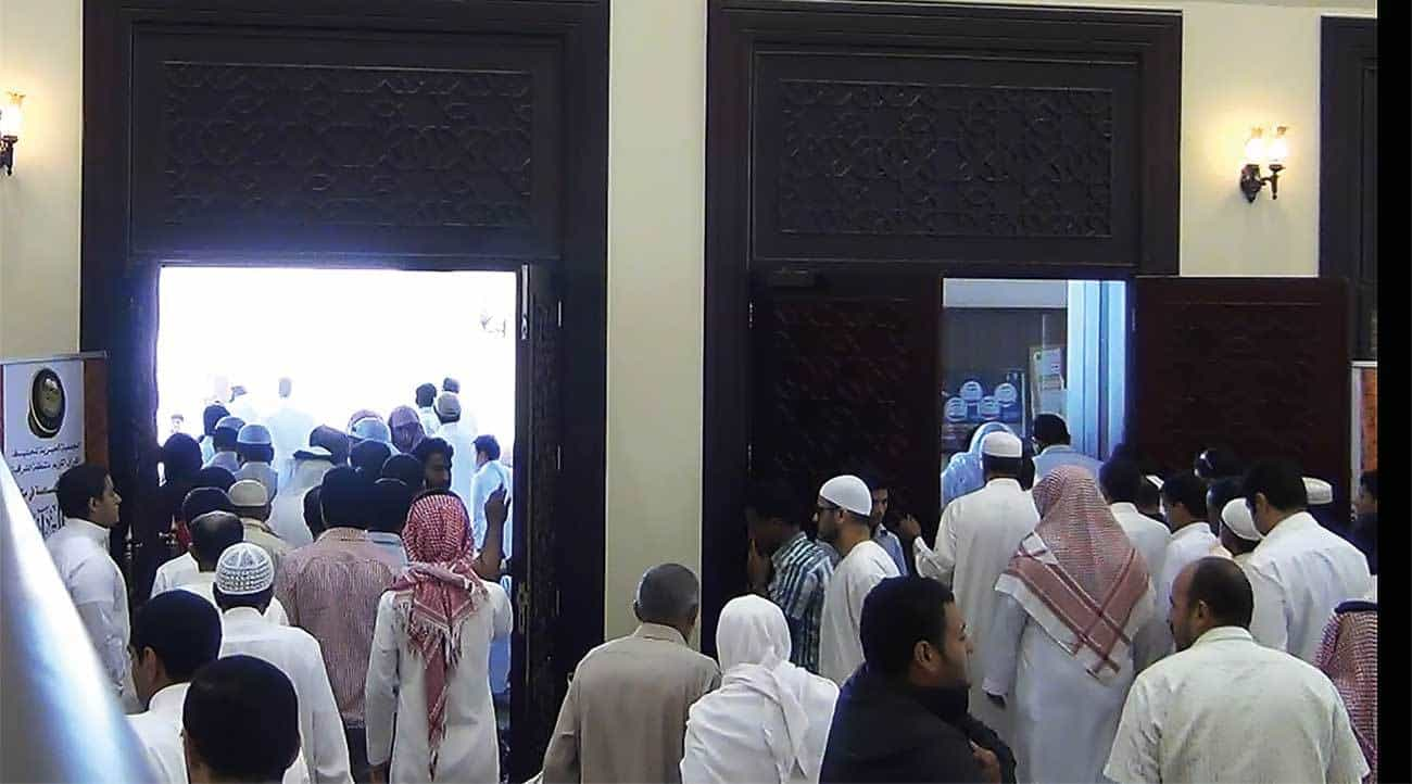 Crowd exiting through main entrance of mosque (exit not code compliant).