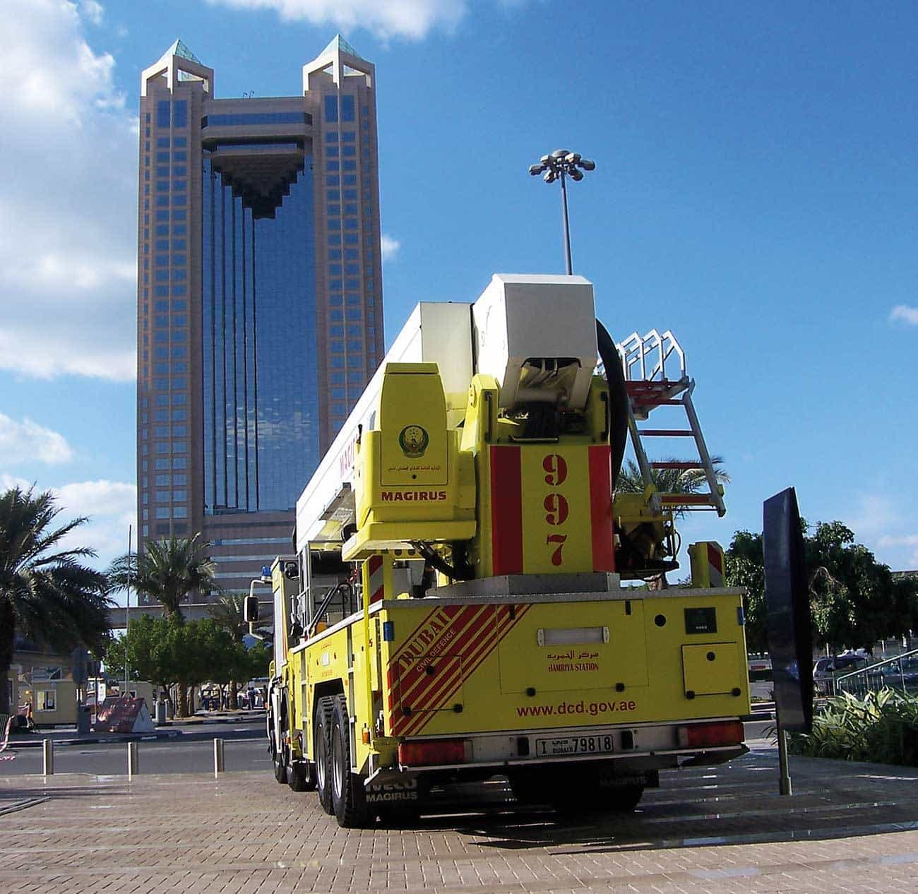 A Dubai Civil Defence 54 metre 8 x 4 Iveco Magirus Aerial Ladder Platform pictured in front of one of Dubai's iconic high rise towers, the Fairmont Hotel in Sheikh Zayed Road.