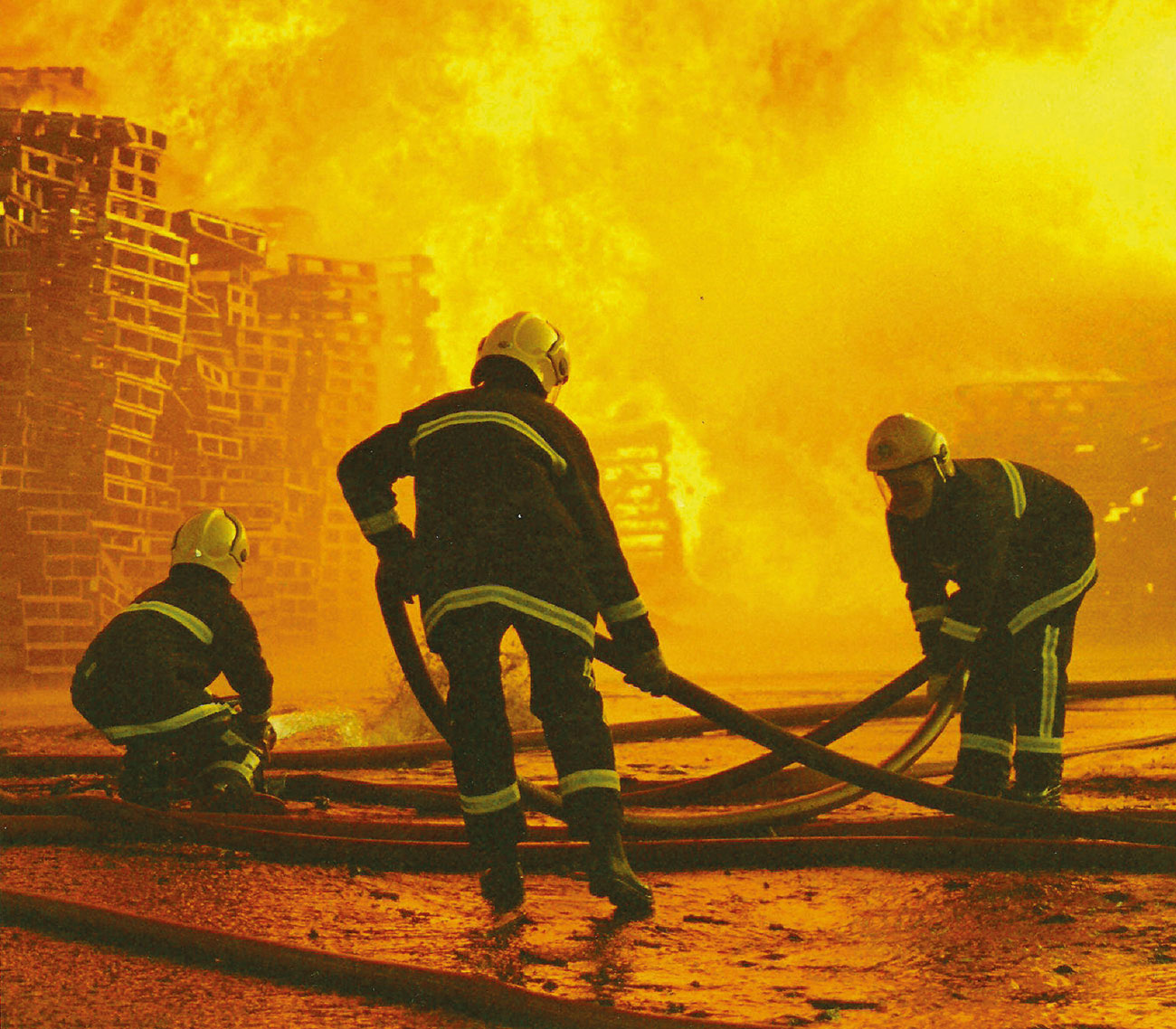 Firefighters from West Yorkshire Fire and Rescue Service tackling a large fire at a wood yard.
